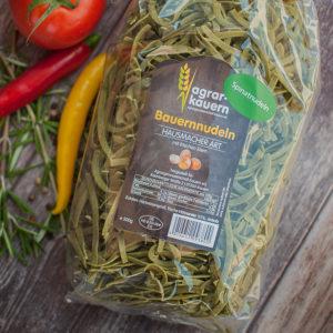 Spinat-Nudeln in der Tüte zwischen Tomaten, Peperoni, Rosmarin und bunten Pfefferkörnern auf braun gemasertem Holzuntergrund